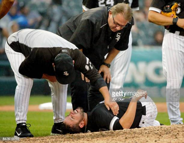 James Shields of the Chicago White Sox is checked on by manager Rick Renteria and head trainer Herman Schneider after being hit in the right leg by a...