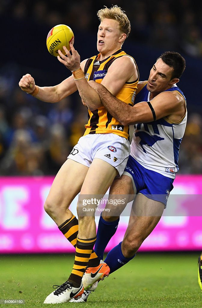 James Sicily of the Hawks handballs whilst being tackled by Michael Firrito of the Kangaroos during the round 13 AFL match between the North Melbourne Kangaroos and the Hawthorn Hawks at Etihad Stadium on June 17, 2016 in Melbourne, Australia.