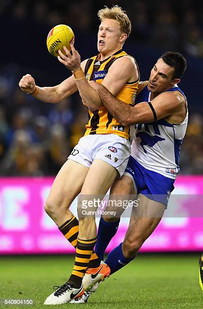 James Sicily of the Hawks handballs whilst being tackled by Michael Firrito of the Kangaroos during the round 13 AFL match between the North...