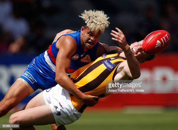 James Sicily of the Hawks is taken high by Jason Johannisen of the Bulldogs during the AFL 2018 JLT Community Series match between the Western...