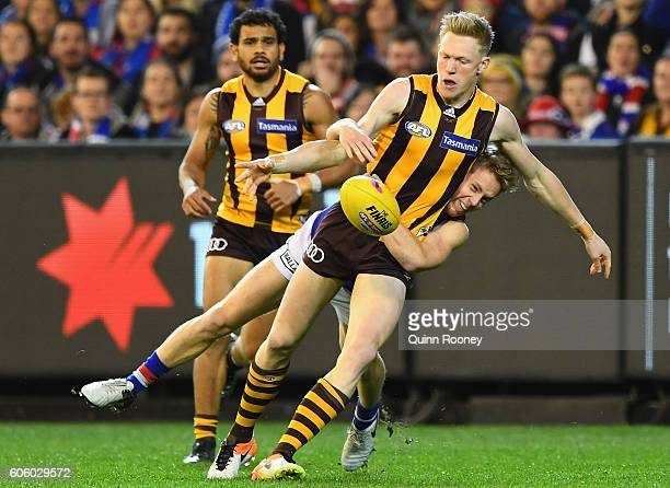 James Sicily of the Hawks kicks whilst being tackled by Lachie Hunter of the Bulldogsduring the second AFL semi final between Hawthorn Hawks and...