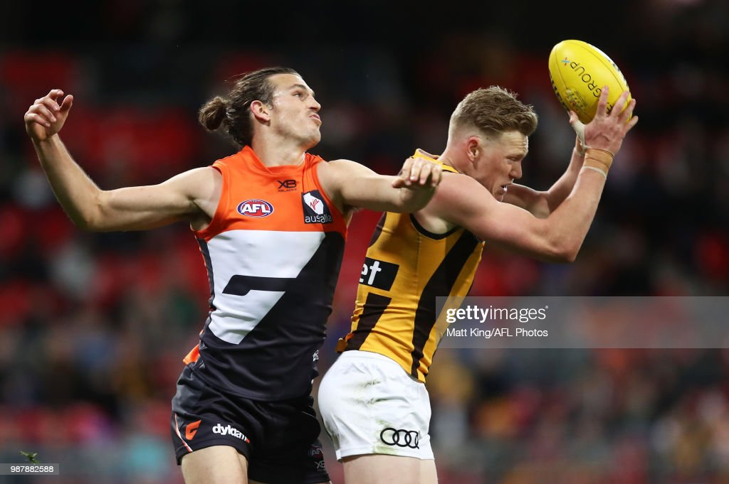 James Sicily of the Hawks takes a mark under pressure from Phil Davis of the Giants during the round 15 AFL match between the Greater Western Sydney Giants and the Hawthorn Hawks at Spotless Stadium on June 30, 2018 in Sydney, Australia.