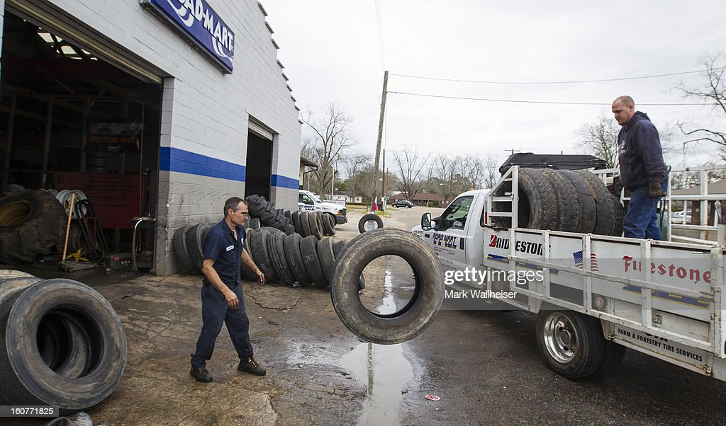 James Stafford (L) and Brent White unload semi truck tires to be recapped at Road Mart in on February 5, 2013 in Midland City, Alabama. The small town of Midland City, Alabama is getting back to normal after a 5 year old boy named Ethan was abducted from a school bus and held hostage for 6 days in this southwest Alabama town and was rescued when the FBI stormed the bunker killing suspect, Jimmy Lee Dykes.