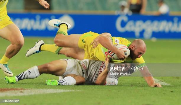 James Stannard of Australia is tackled in the game with the US during the Sydney World Rugby Sevens Series tournament in Sydney on January 26 2018 /...