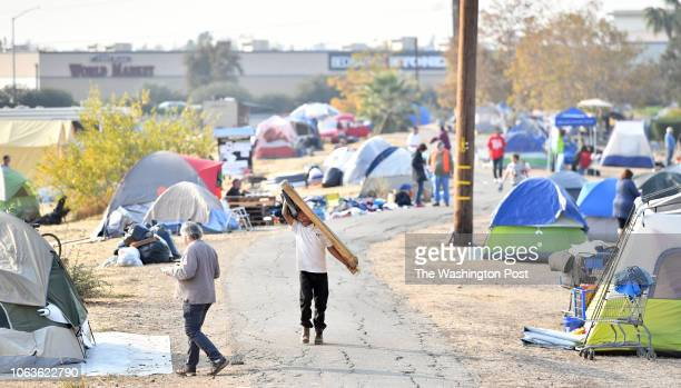 James Steen carries wood back to his tent to prepare his temporary home for an expected rainstorm at an evacuee encampment at a Walmart parking lot...