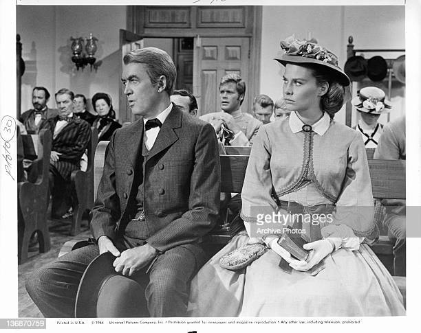 James Stewart and Rosemary Forsyth sit in church next to each other in a scene from the film 'Shenandoah' 1965