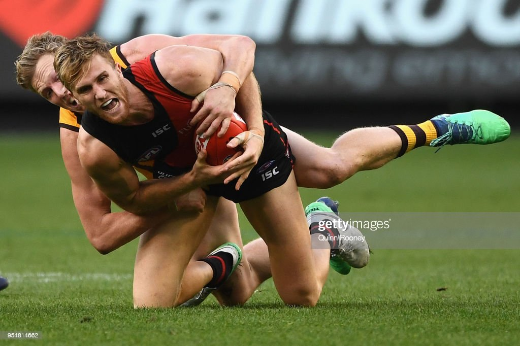 James Stewart of the Bombers is tackled by James Sicily of the Hawks during the round seven AFL match between the Essendon Bombers and the Hawthorn Hawks at Melbourne Cricket Ground on May 5, 2018 in Melbourne, Australia.