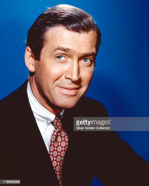James Stewart US actor weaing a black jacket white shirt and red patterned tie in a studio portrait against a blue background circa 1955