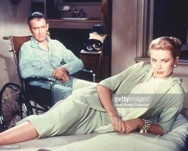 James Stewart , US actor, wearing pyjamas as he sits in his wheelchair, while Grace Kelly , US actress, lays on a bed in a publicity still issued for...