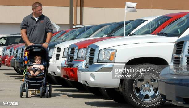 James Stout pushes his 10monthold daughter Allison in a stroller as he shops for a Dodge Dakota at the Dellen Automotive Family dealership in...