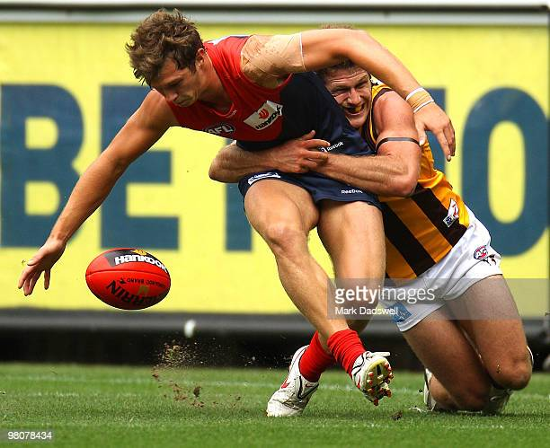 James Strauss of the Demons is tackled by Campbell Brown of the Hawks during the round one AFL match between the Melbourne Demons and the Hawthorn...