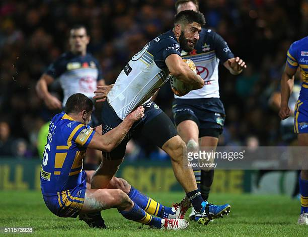 James Tamou of North Queensland Cowboys is tackled by Brett Ferres of Leeds Rhinos during the World Club Series match between Leeds Rhinos and North...