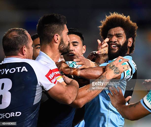 James Tamou of the Cowboys gets involved in a melee with Junior Roqica of the Sharks during the round 25 NRL match between the North Queensland...