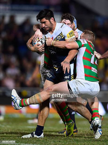 James Tamou of the Cowboys is tackled by Jason Clark and Chris McQueen of the Rabbitohs during the round 23 NRL match between the North Queensland...