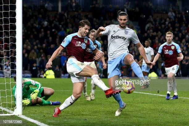 James Tarkowski of Burnley clears the ball as he is challenged by Andy Carroll of West Ham United during the Premier League match between Burnley FC...