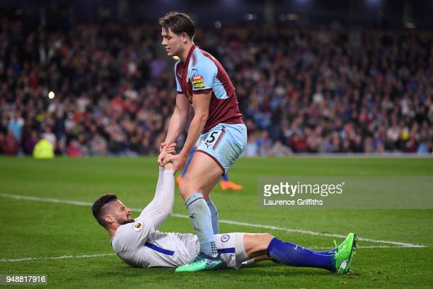 James Tarkowski of Burnley helps Olivier Giroud of Chelsea to stand up during the Premier League match between Burnley and Chelsea at Turf Moor on...