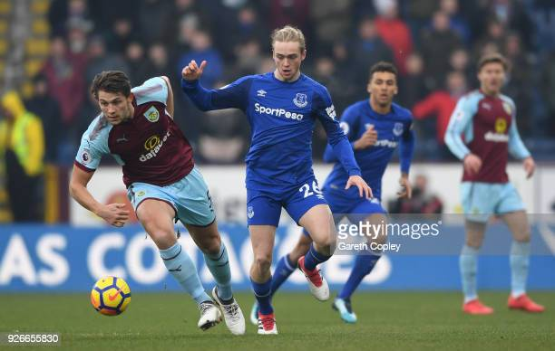 James Tarkowski of Burnley runs with the ball away from Tom Davies of Everton during the Premier League match between Burnley and Everton at Turf...