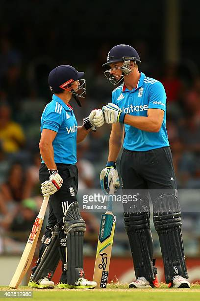James Taylor and Jos Buttler of England touch gloves during the One Day International match between England and India at WACA on January 30 2015 in...
