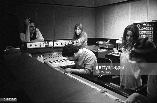 James Taylor recording engineer Hank Cicalo Joni Mitchell Carole King and record producer Lou Adler gather around the mixing desk for a playback in...