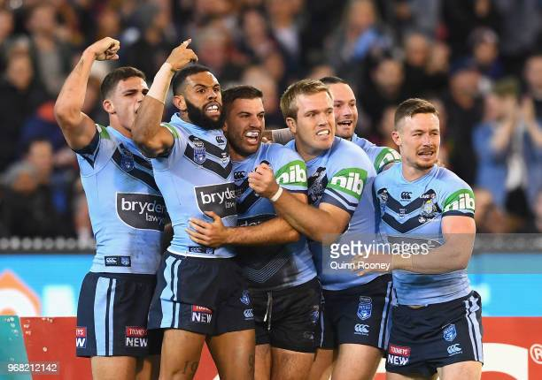 James Tedesco of the Blues is congratulated by team mates after scoring a try during game one of the State Of Origin series between the Queensland...