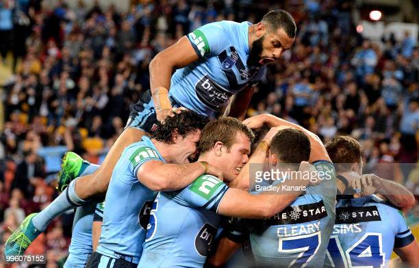 James Tedesco of the Blues is congratulated by team mates after scoring a try during game three of the State of Origin series between the Queensland...