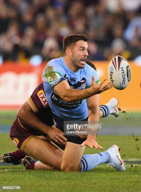 James Tedesco of the Blues passes the ball whilst being tackled during game one of the State Of Origin series between the Queensland Maroons and the...