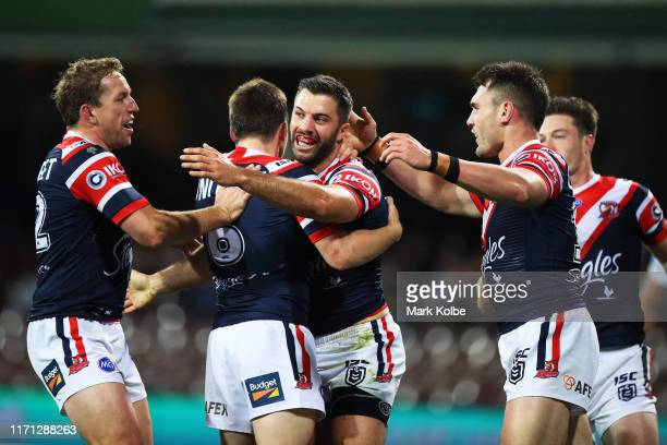 James Tedesco of the Roosters celebrates with team mates after scoring a try during the round 24 NRL match between the Sydney Roosters and the...