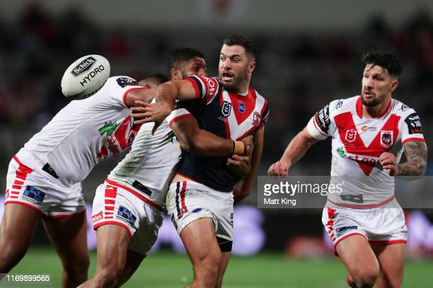 James Tedesco of the Roosters offloads the ball in a tackle during the round 23 NRL match between the St George Illawarra Dragons and the Sydney...