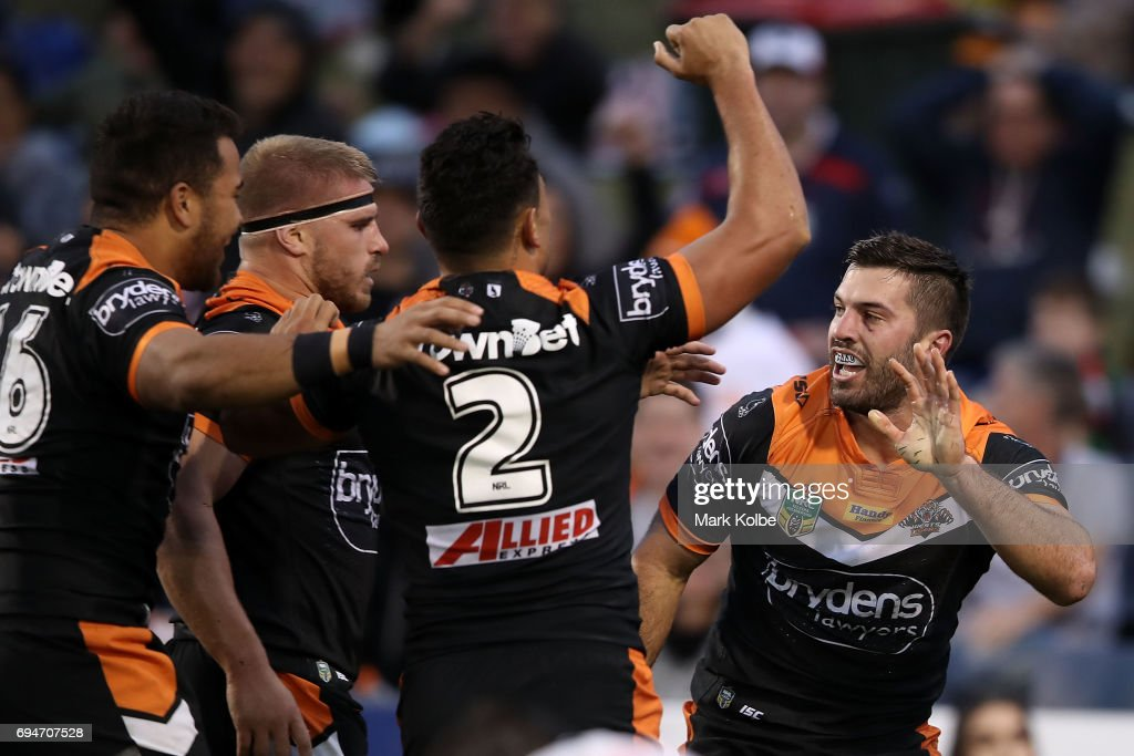 James Tedesco of the Tigers celebrates with his team mates after scoring a try during the round 14 NRL match between between the Wests Tigers and the Sydney Roosters at Campbelltown Sports Stadium on June 11, 2017 in Sydney, Australia.