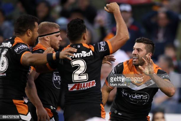 James Tedesco of the Tigers celebrates with his team mates after scoring a try during the round 14 NRL match between between the Wests Tigers and the...