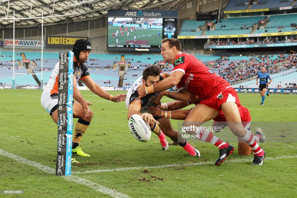 James Tedesco of the Tigers drops the ball over the line as Jason Nightingale of the Dragons defends during the round five NRL match between the Wests Tigers and the St George Illawarra Dragons at ANZ Stadium on April 2, 2017 in Sydney, Australia.