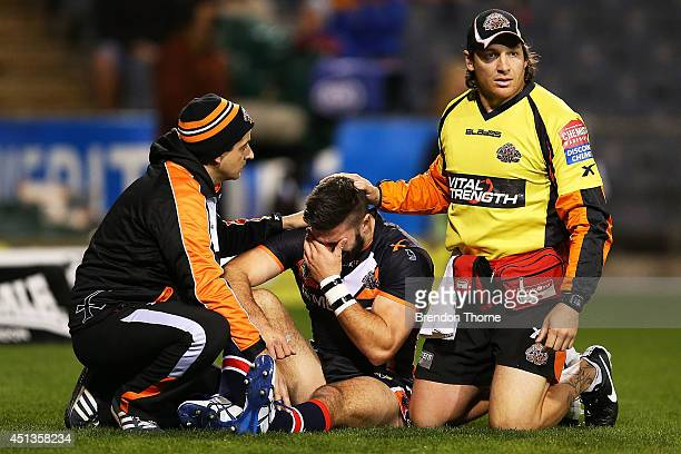 James Tedesco of the Tigers is consoled by trainers after sustaining an injury in the opening minutes during the round 16 NRL match between the Wests...