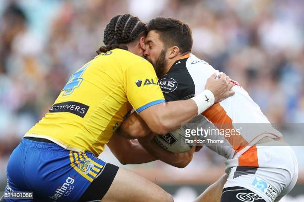 James Tedesco of the Tigers is tackled by Brad Takairangi of the Eels during the round 20 NRL match between the Wests Tigers and the Parramatta Eels...