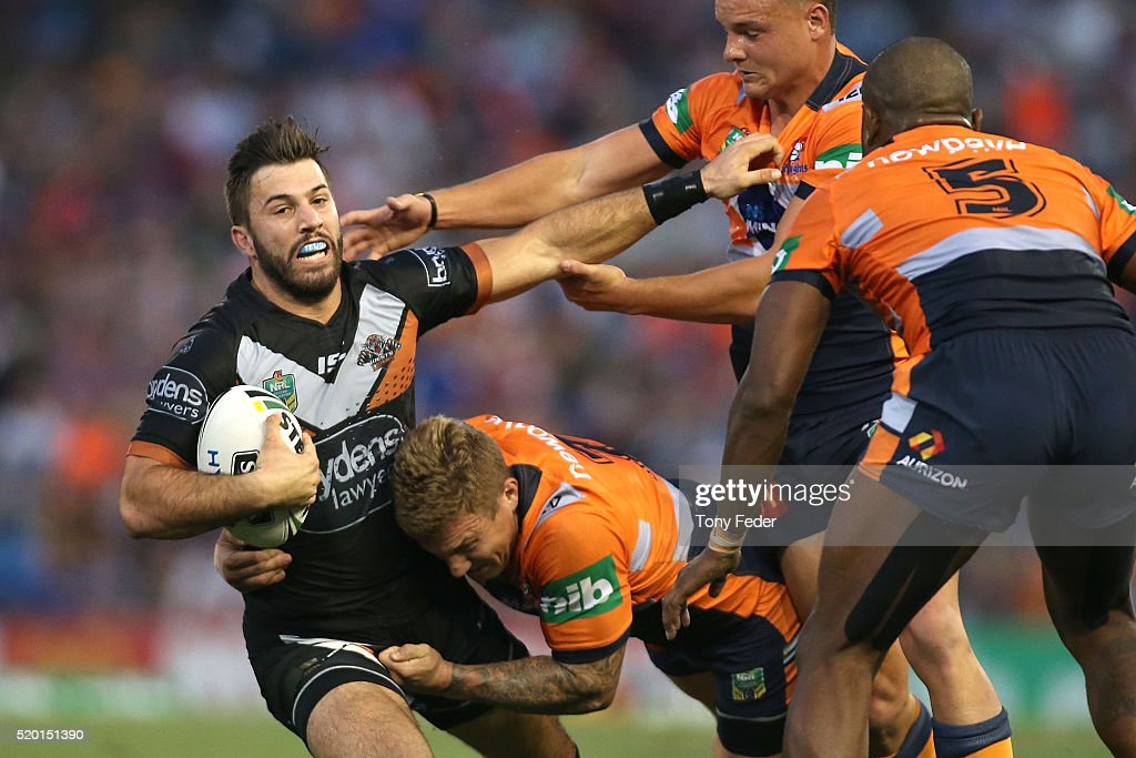 James Tedesco of the Tigers is tackled by Trent Hodkinson of the Knights during the round six NRL match between the Newcastle Knights and the Wests Tigers at Hunter Stadium on April 10, 2016 in Newcastle, Australia.