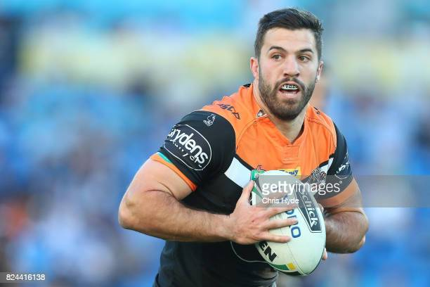 James Tedesco of the Tigers runs the ball during the round 21 NRL match between the Gold Coast Titans and the Wests Tigers at Cbus Super Stadium on...