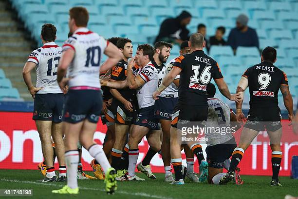 James Tedesco of the Wests Tigers celebrates with his team mates after scoring a try during the round 20 NRL match between the Wests Tigers and the...
