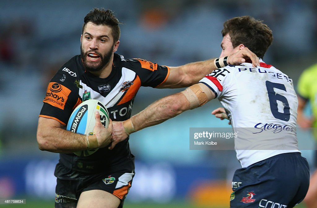 James Tedesco of the Wests Tigers fends off James Maloney of the Roosters during the round 20 NRL match between the Wests Tigers and the Sydney Roosters at ANZ Stadium on July 24, 2015 in Sydney, Australia.