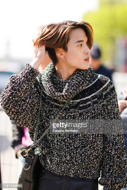 James Teeradon Supapunpinyo wears a black flecked sweater a black Chanel alligator pattern bag outside the Chanel Cruise Collection 2020 At Grand...