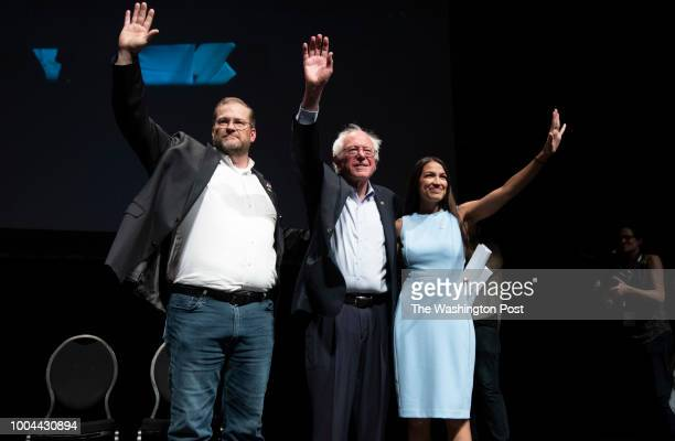 James Thompson Senator Bernie Sanders and Alexandria OcasioCortez wave to the crowd at the end of a campaign rally in Wichita Kansas on July 20 2018