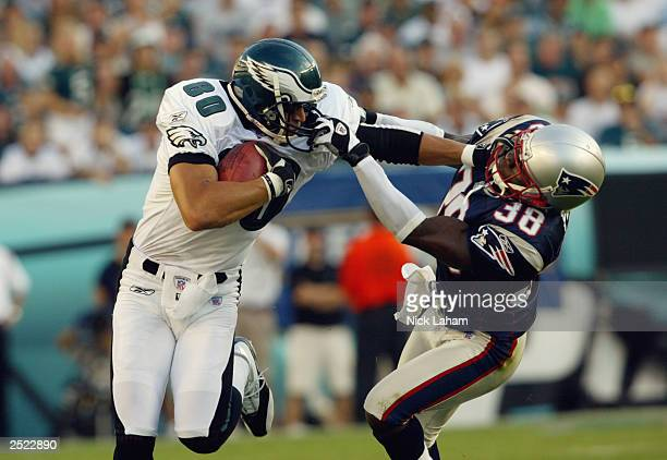 James Thrash of the Philadelphia Eagles stiffarms Tyrone Poole of the New England Patriots on September 14 2003 at Lincoln Financial Field in...