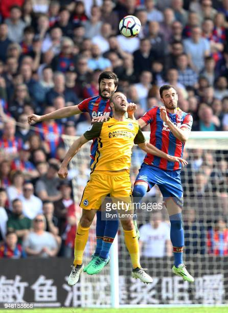 James Tomkins of Crystal Palace Glenn Murray of Brighton and Hove Albion and Luka Milivojevic of Crystal Palace compete for a header during the...