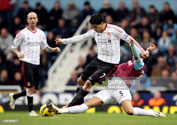 James Tomkins of West Ham tackles Luis Suarez of Liverpool during the Barclays Premier League match between West Ham United and Liverpool at the...
