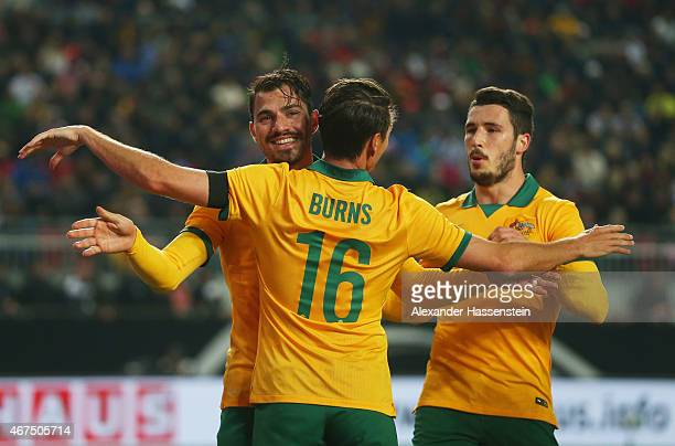 James Troisi of Australia celebrates with team mates Nathan Burns and Matthew Leckie as he scores their first and equalising goal during the...