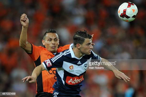 James Troisi of the Victory competes for the ball with Jade North of the Roar during the A-League Semi Final match between the Brisbane Roar and...