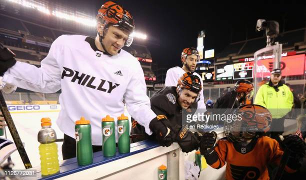 James van Riemsdyk Ivan Provorov and Justin Bailey of the Philadelphia Flyers stand at their team's bench during their practice in preparation for...