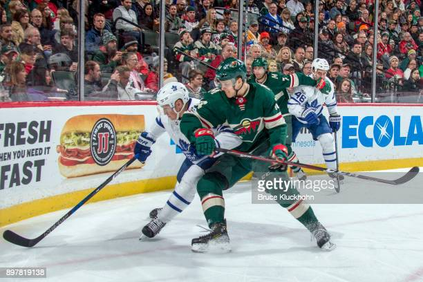 James van Riemsdyk of the Toronto Maple Leafs and Joel Eriksson Ek of the Minnesota Wild battle for the puck during the game at the Xcel Energy...