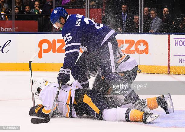 James van Riemsdyk of the Toronto Maple Leafs and Mike Fisher of the Nashville Predators slide into Predators goalie Marek Mazanec during the first...