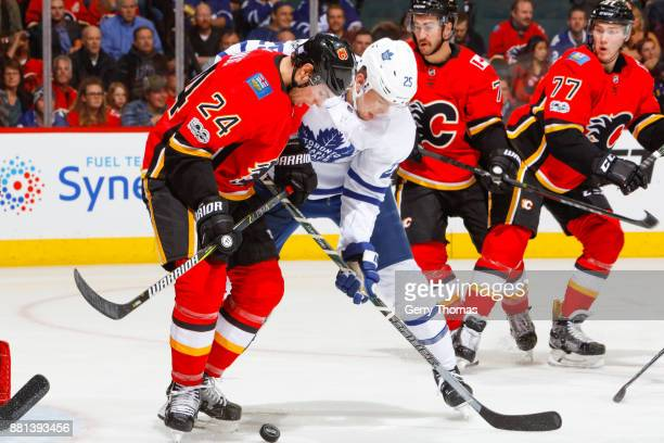 James van Riemsdyk of the Toronto Maple Leafs and Travis Hamonic of the Calgary Flames battle for the puck in an NHL game against the Toronto Maple...