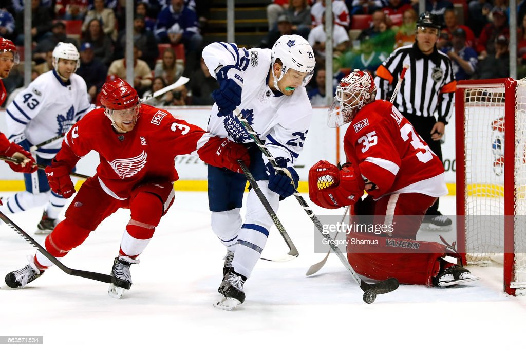 James van Riemsdyk #25 of the Toronto Maple Leafs controls the puck just before scoring a third period goal between Jimmy Howard #35 and Nick Jensen #3 of the Detroit Red Wings at Joe Louis Arena on April 1, 2017 in Detroit, Michigan.