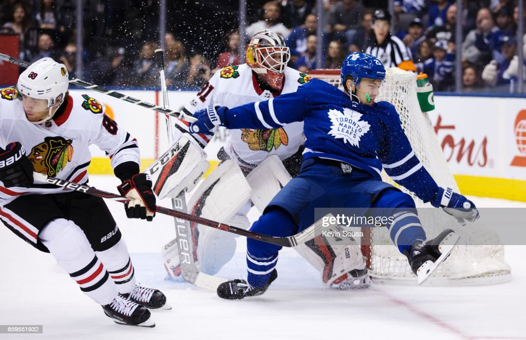 James van Riemsdyk #25 of the Toronto Maple Leafs falls into Anton Forsberg #31 of the Chicago Blackhawks during overtime October 9, 2017 at the Air Canada Centre in Toronto, Ontario, Canada.